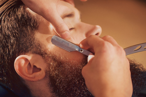Professional barber shaving beard of his client