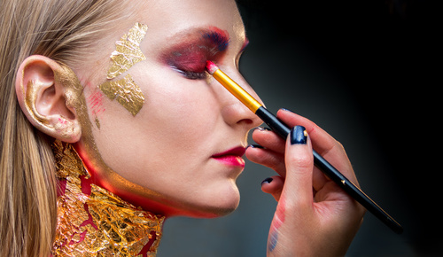 Artistic professional make up applies eye shadow. Beautiful woma